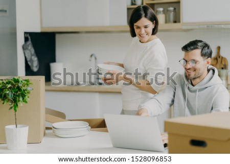 Moving house and real estate. Caring brunette woman holds pile of plates, unpacks personal belonging Stock photo © vkstudio