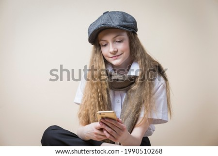 Blond schoolgirl girl with curly hair with a black hat on her head Stock photo © ElenaBatkova