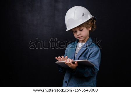 Serious cute little boy in hardhat and formalwear using digital tablet Stock photo © pressmaster