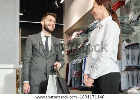 Young cheerful businessman with paperbags saying thanks to shop assistant Stock photo © pressmaster