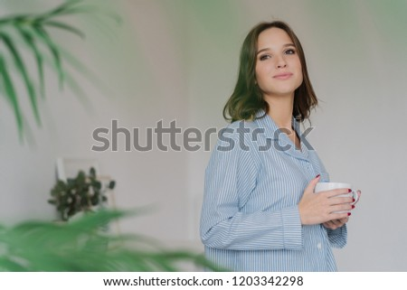 Sideways shot of dreamy Caucasian woman dressed in casual clothes, drinks tea, stands indoor against Stock photo © vkstudio