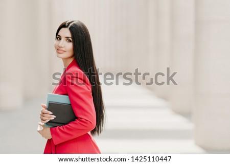 Sideways shot of elegant brunette lady with dark long straight hair, dressed in fashionable red suit Stock photo © vkstudio