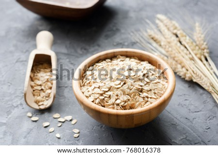 Oat flakes in ceramic bowls and wooden spoon, golden wheat ears  Stock photo © marylooo
