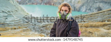 BANNER, LONG FORMAT Young woman tourist sitting at the edge of the crater of the Ijen volcano or Kaw Stock photo © galitskaya