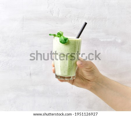 Man hold in hand glass with healthy detox smoothie, cooking with blender Stock photo © Illia
