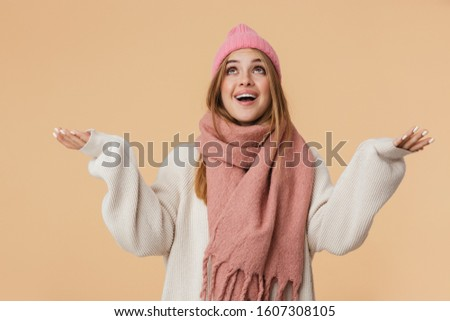 Image of girl wearing winter hat looking upward with arms wide o Stock photo © deandrobot