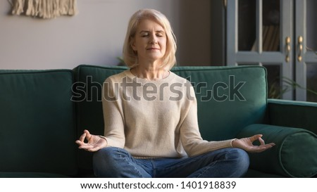 Attractive senior woman working out at home, doing yoga or pilates exercise Stock photo © Illia