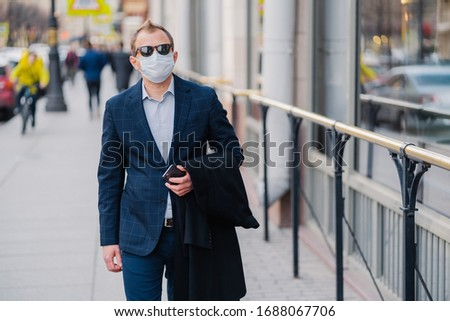 Outdoor shot of businessman in formal clothes, holds modern cell phone in hands, walks on street, pr Stock photo © vkstudio