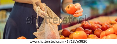 A woman chooses tomatoes in a supermarket without using a plastic bag. Reusable bag for buying veget Stock photo © galitskaya