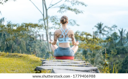 Young woman on path into the tropical jungle in yoga lotus pose Stock photo © Kzenon