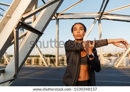 Photo of nice athletic woman using earpods and doing exercise Stock photo © deandrobot