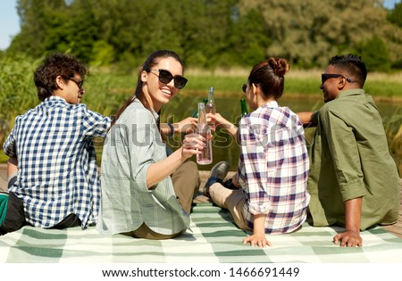 friends drinking beer and cider on lake pier Stock photo © dolgachov