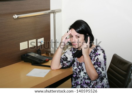 Stressed businesswoman holding her forehead while speaking on th Stock photo © dacasdo