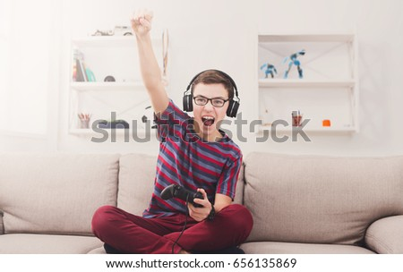 Portrait of happy teenage gamer boy winning while playing video  Stock photo © deandrobot