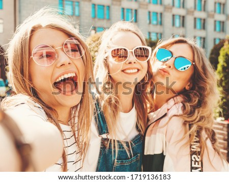 Pretty woman 20s in sunglasses smiling and taking photo on retro Stock photo © deandrobot