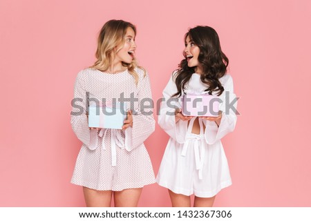 Shocked happy young woman posing isolated over pink wall background holding lipstick. Stock photo © deandrobot