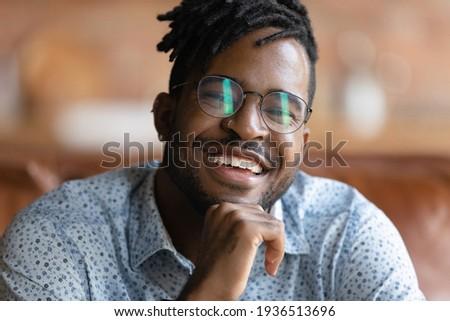 Portrait of happy african guy having stylish afro hairdo smiling Stock photo © deandrobot