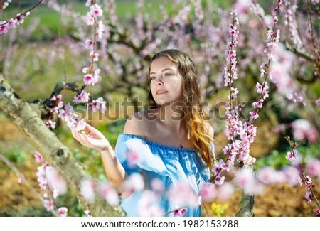 beautiful girl posing in the pink peach and sakura flowers blooming garden young attractive woman s stock photo © elenabatkova