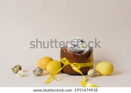 Slice of easter bread with colorful eggs and yellow tulips on blue wooden background Stock photo © Melnyk