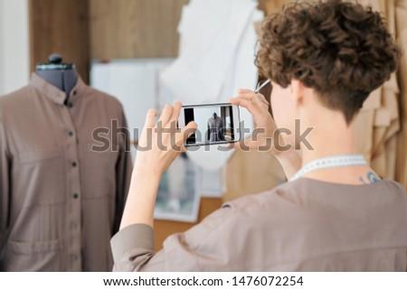 Young woman making shot of unfinished dress or jacket on dummy Stock photo © pressmaster