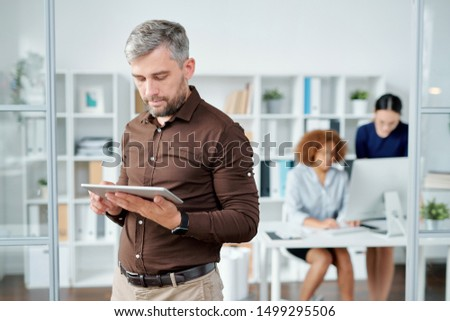 Elegante barbuto imprenditore touchpad guardando schermo Foto d'archivio © pressmaster