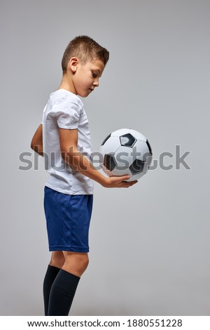 Side view of smiling schoolboy holding football in classroom of elementary school Stock photo © wavebreak_media
