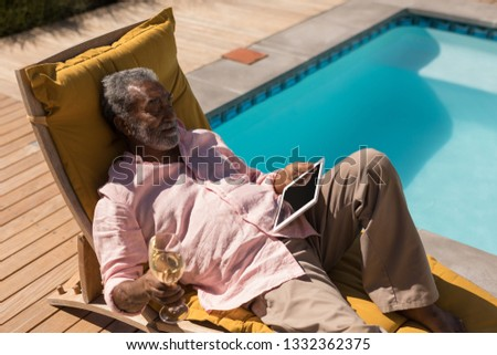 high angle view of senior man relaxing on sun lounger and reading a book on beach in the sunshine stock photo © wavebreak_media