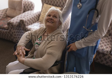 High angle view of female doctor interacting with disabled senior woman on wheelchair in living room Stock photo © wavebreak_media