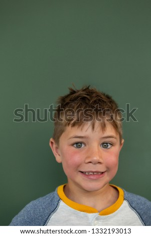 Front view of Caucasian schoolboy standing against green chalkboard in a classroom at elementary sch Stock photo © wavebreak_media