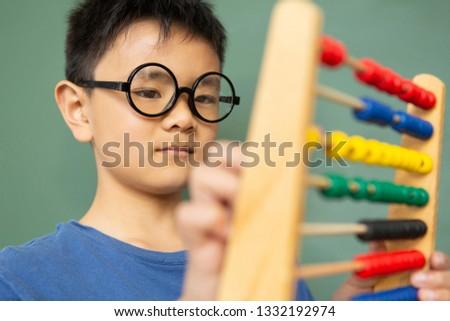 Close-up of Asian boy learning math with abacus against green chalkboard in a classroom at elementar Stock photo © wavebreak_media