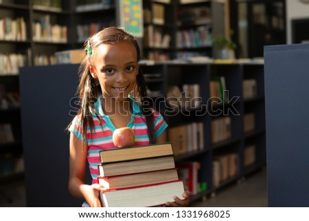 Front view of happy mixed-race schoolgirl holding stack of books and apple in the library at home Stock photo © wavebreak_media