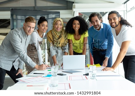 Front view of standing mixed race business colleagues discussing over blueprint in modern office Stock photo © wavebreak_media