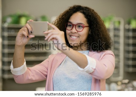 Happy intercultural girl in eyeglasses holding smartphone in front of her face Stock photo © pressmaster