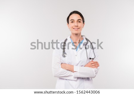 Pretty young confident clinician in whitecoat holding clipboard with document Stock photo © pressmaster