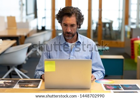Front view of Caucasians business executives using laptop sitting on the sofa in modern office Stock photo © wavebreak_media