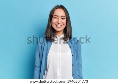 Horizontal shot of pleasant looking dark haired woman in knitted sweater looks tenderly at camera, e Stock photo © vkstudio