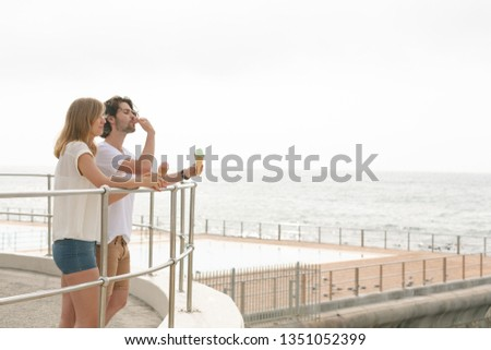 Side view of young Caucasian couple standing at promenade while having ice cream cone  Stock photo © wavebreak_media