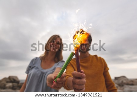 Front view of young Caucasian couple playing with fire cracker while standing at beach. They are smi Stock photo © wavebreak_media