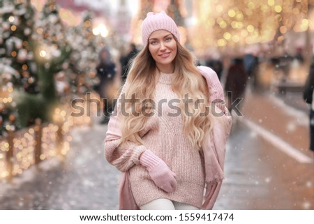 Woman in winter clothes in a pink sweater walks around the New Year decorated city Stock photo © ElenaBatkova