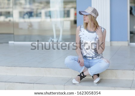 A woman in casual clothes sits on the steps near the shop Windows Stock photo © ElenaBatkova