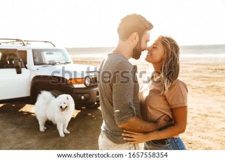 Woman hugging dog samoyed outdoors at the beach in car. Stock photo © deandrobot