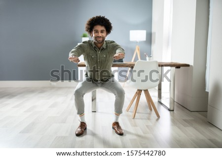 Smiling Young Businessman Doing Sit-ups Stock photo © AndreyPopov