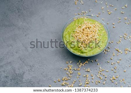 Horizontal shot of glass bowl with fresh vegetetable green smoothie containig much vitamins, buckwhe Stock photo © vkstudio