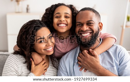 Photo of little daughter embraces her mother and father, plays with pedigree dog, sit at white desk  Stock photo © vkstudio