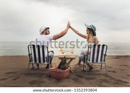 couple drinking cocktails on beach during vacation or honeymoon in tropics Stock photo © Kzenon