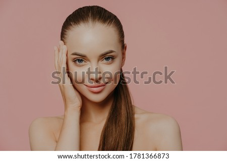 Isolated shot of pretty woman with combed pony tail, enjoys freshness of skin, looks with charming e Stock photo © vkstudio