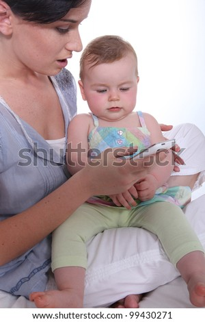 Mother resting baby on knee whilst looking at mobile telephone Stock photo © photography33