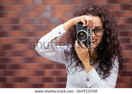 Attractive woman using a camera while standing against a white background stock photo © wavebreak_media