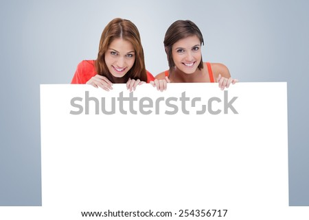 Smiling attractive teenager holding a blank poster while looking in front of her stock photo © wavebreak_media