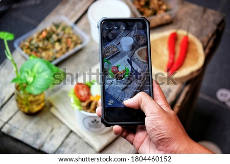 Mans hand take a photo of freshly prepared homemade salad with natural ingredients by smartphone abo Stock photo © artjazz